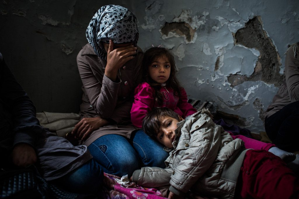 "Syrian refugees Aya, 8, and Layth, 6, from Aleppo, pictured with their mother, Fatima (not her real name) at a train station in Slanishte, Macedonia, on the border with Serbia. The children's father is still in Syria. Fatima says, ""I am scared to travel as a lone woman with no man to protect us. The children cry all the time and say they want to go back. The most difficult part of our journey has been here in Macedonia, we were very afraid crossing the border because we heard that gangs might attack us. And now the weather has been very bad but thank God we found shelter here."" ; Travelling with groups of Syrian refugees who are making their way through the former Yugoslav Republic of Macedonia (fYROM) towards Serbia and on to Germany and Scandinavia. Regulations in Greece prohibit asylum-seekers from residing in border regions. The large group of Syrian refugees, numbering around 400, had spent the previous day walking through the rain and finally found shelter at the train station late in the evening. Hundreds of refugees and migrants are traveling through Macedonia everyday on their way north through the Balkans, in an attempt to reach western Europe. They use whatever means of transport is available including trains and bicycles, however many end up walking the entire distance"